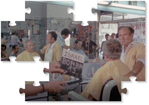 """Dreharbeiten: Zwei Männer in einem Friseusalon. Im Vordergrund wird eine Filmklappe mit der Aufschrift """"Israel Bomba 13"""" gehalten. Im Spiegel sind weitere Personen im Friseursalon erkennbar."""
